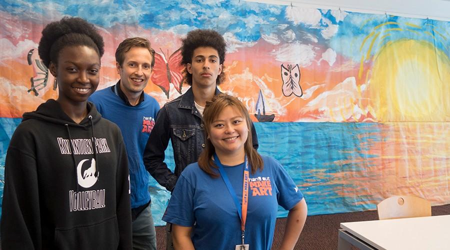 Teens standing in front of mural in teen lounge