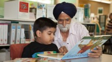 Boy reading at a table with grandfather